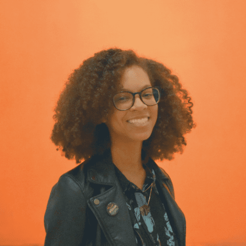 Headshot of person with glasses smiling against an orange background
