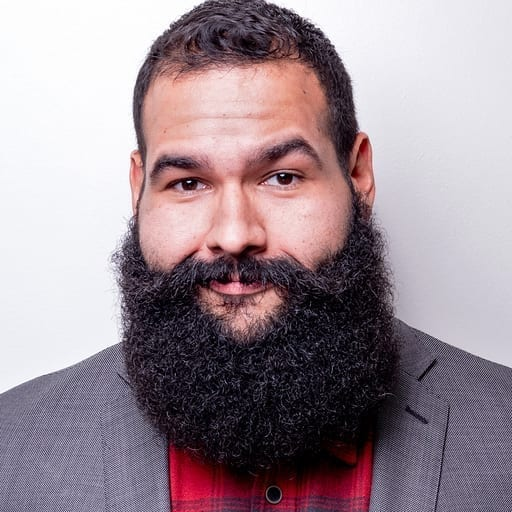 Headshot of person with large beard in a gray suit smiling.